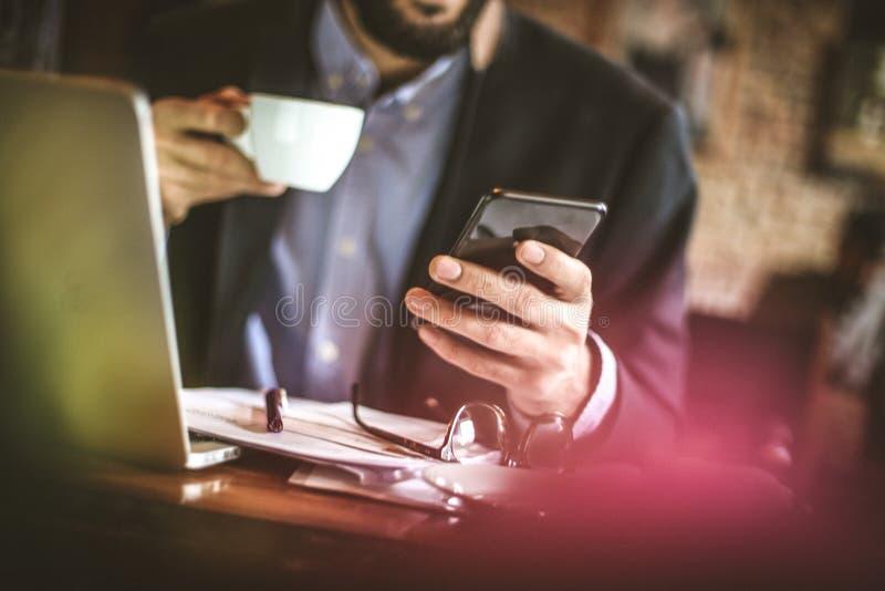 Affärsmannen tar ett avbrott som direktanslutet surfar på den smarta telefonen royaltyfri foto