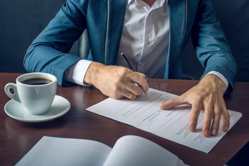 Affärsmannen undertecknar viktiga lagliga dokument på skrivbordet med koppen kaffe arkivfoto