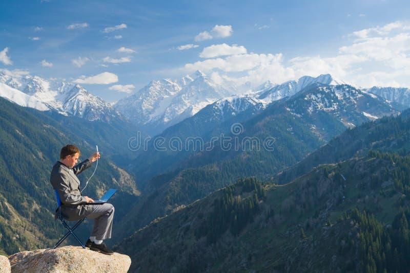 Affärsmannen upptill av berget genom att använda trådlös networ arkivbilder