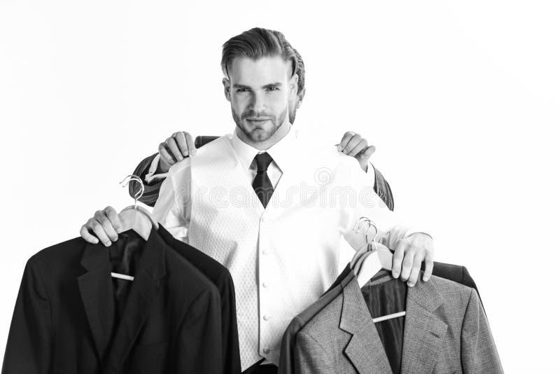 Affärsmannen väljer dräkten med händer av assistenten bak honom arkivbild