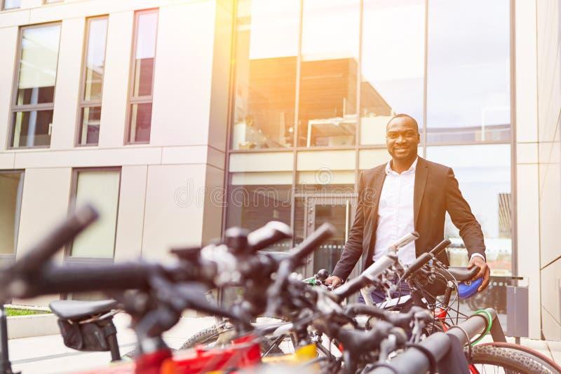 Affärsmannen vänder av cykeln framme av kontoret royaltyfria bilder
