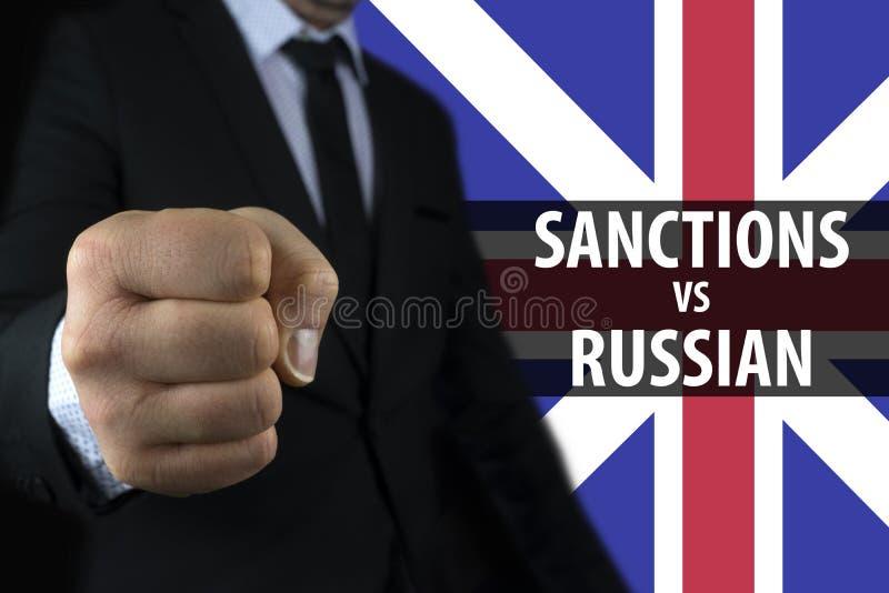 Affärsmannen visar en näve mot bakgrunden av den engelska flaggan och en inskrift av sanktioner mot Ryssland royaltyfria foton