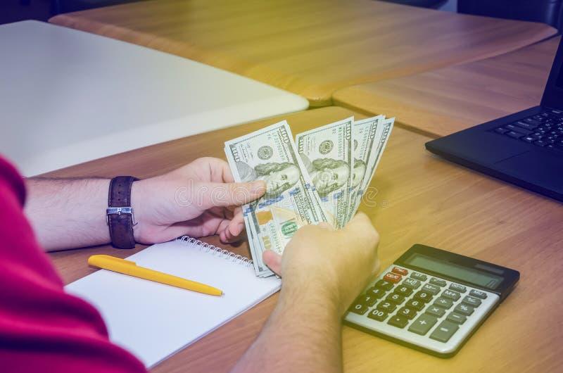 Affärsmannens arbeten för hand för pengarna, erbjuder han sedlar med partnern för investeringaffär, honom räknar dollaren för räk arkivfoton