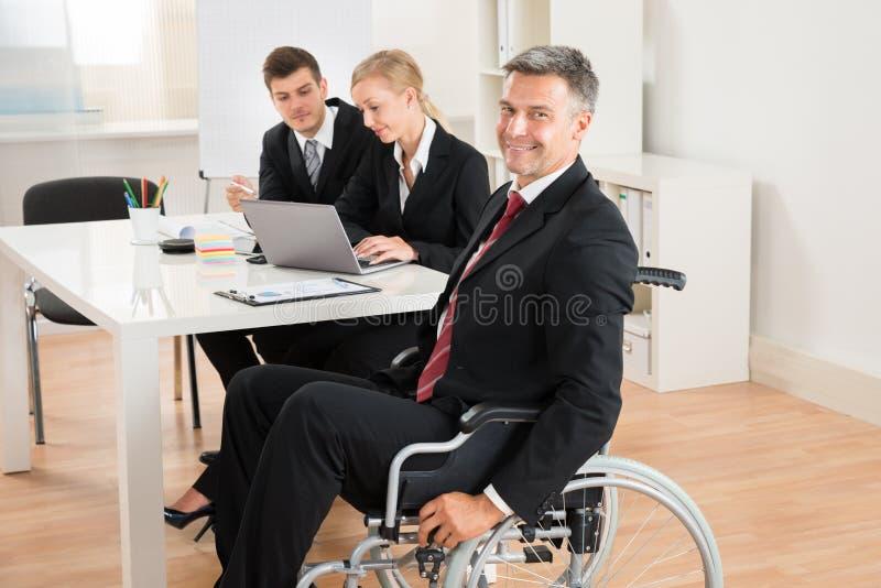AffärsmanOn Wheelchair With kollegor i regeringsställning arkivfoto