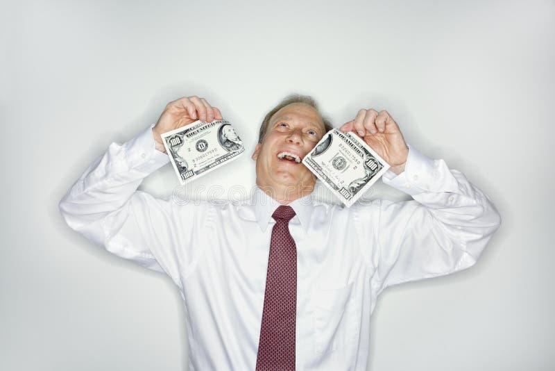 affärsmanpengarslösning arkivfoto