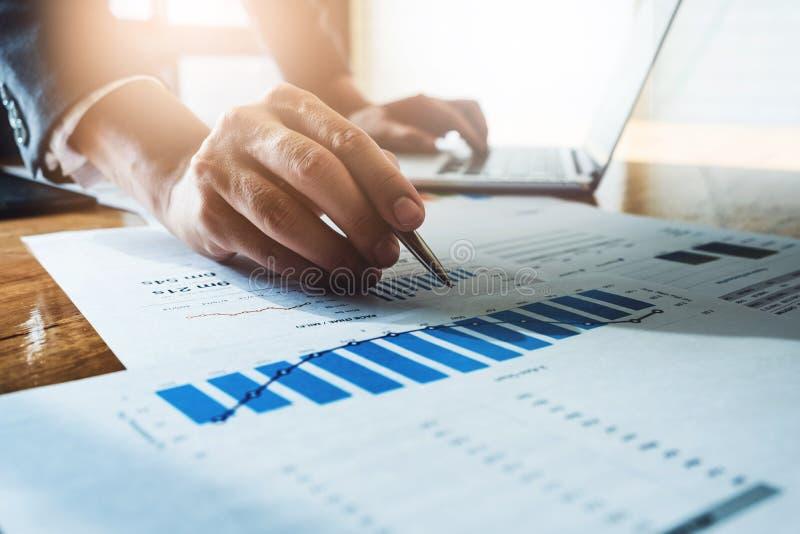 Affärsmanpenna som pekar omsättning med grafdiagramrapporten och oss arkivfoto