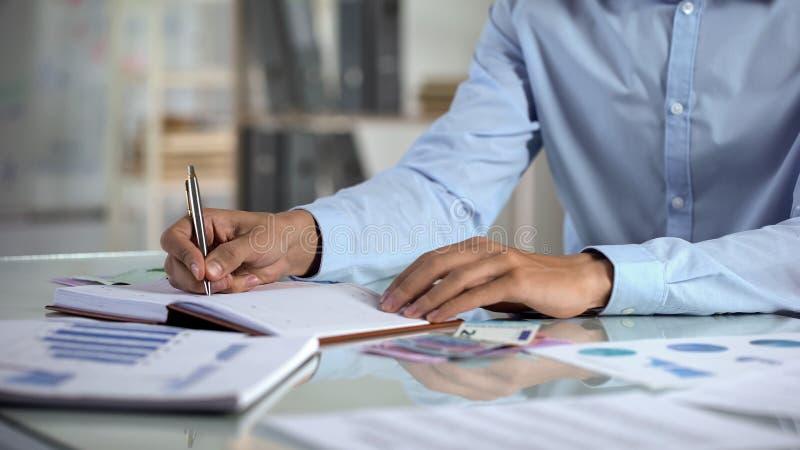 Affärsmanplanläggningsbudget som skriver i anteckningsbok på kontoret, små och medelstora företaginkomst royaltyfri bild