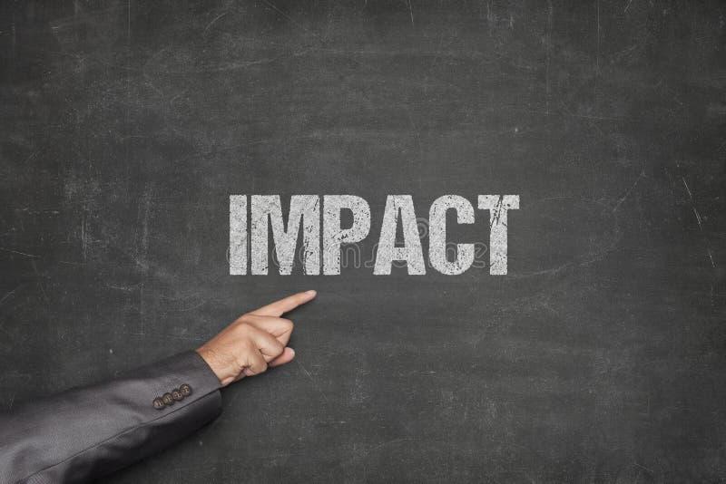 AffärsmanPointing At Impact text på svart tavla royaltyfri fotografi