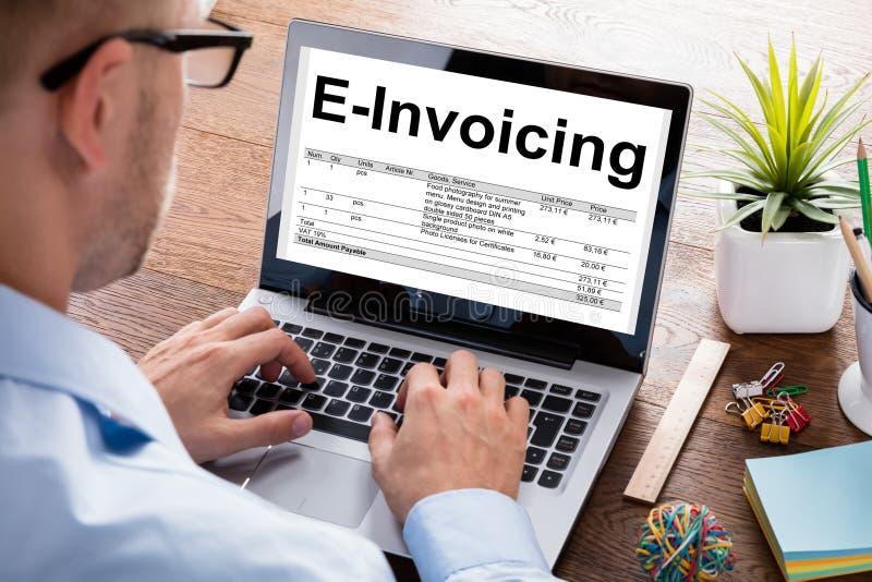 AffärsmanPreparing E-fakturering Bill On Laptop At Desk royaltyfri foto
