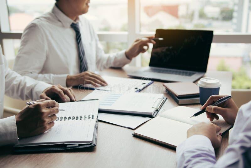 Affärsmanpunkt till bärbara datorn som ser grafen av företagsbokföringsunderlagen i den skärmen och tillsammans analysen för dato royaltyfri bild