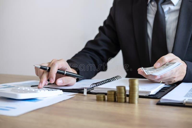 Affärsmanrevisor som räknar pengar och gör anmärkningar på rapporten som gör finanser och att beräkna om kostnad av investeringen arkivbild