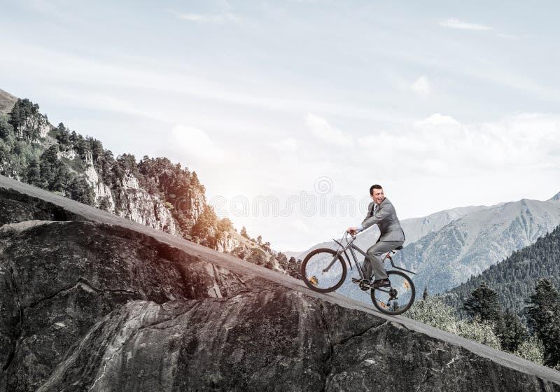 Affärsmanridning som är sluttande med cykeln fotografering för bildbyråer