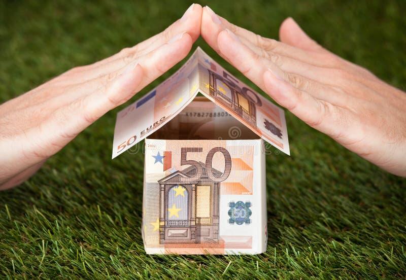 Affärsmans händer som skyddar eurohuset på gräs- land royaltyfria foton