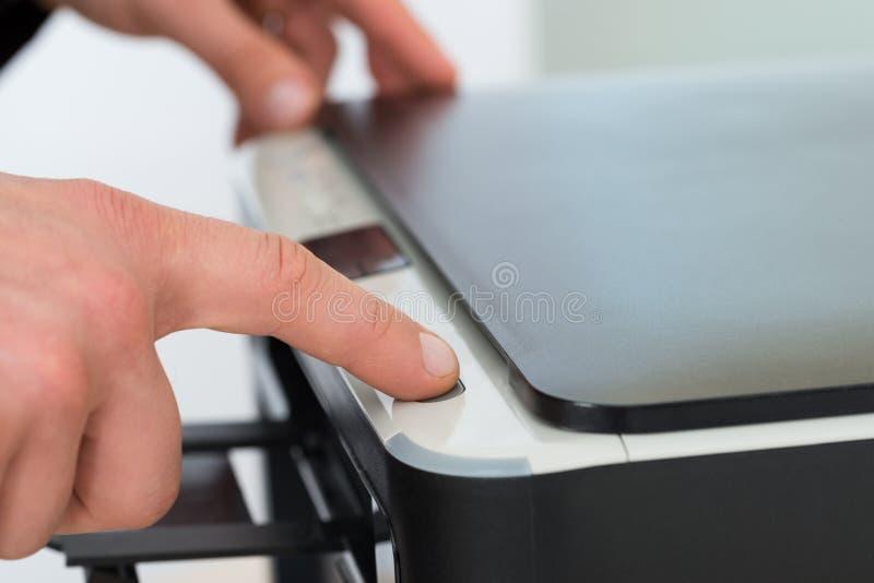 Affärsmans trängande knapp för finger av fotokopiamaskinen royaltyfri fotografi