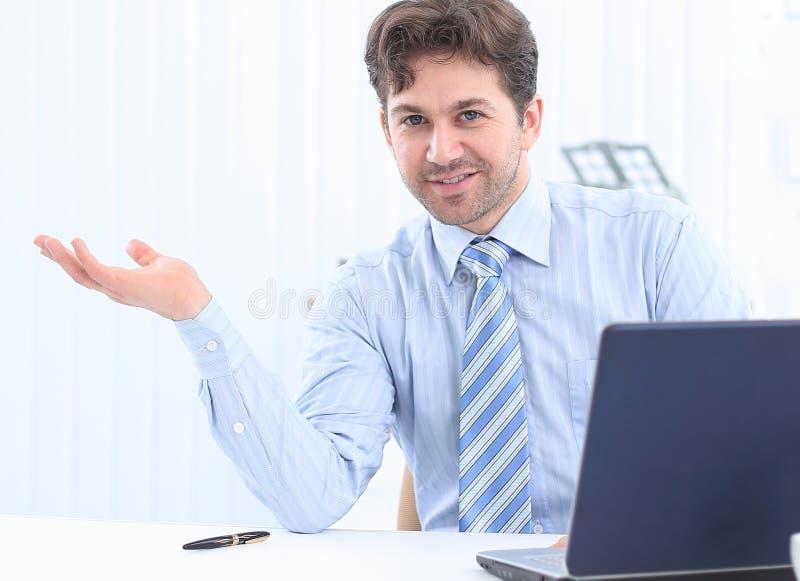 Affärsmansammanträde bak ett skrivbord och peka för att kopiera utrymme fotografering för bildbyråer