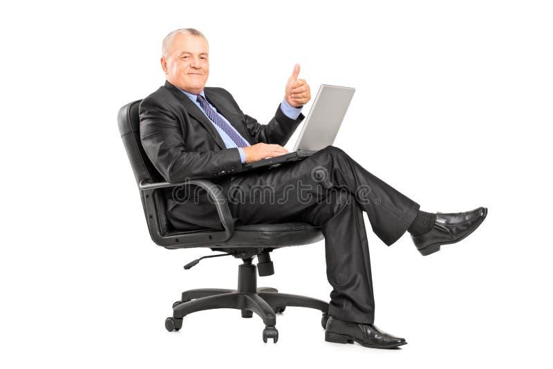 Affärsmansammanträde i en fåtölj med en bärbar dator arkivfoto