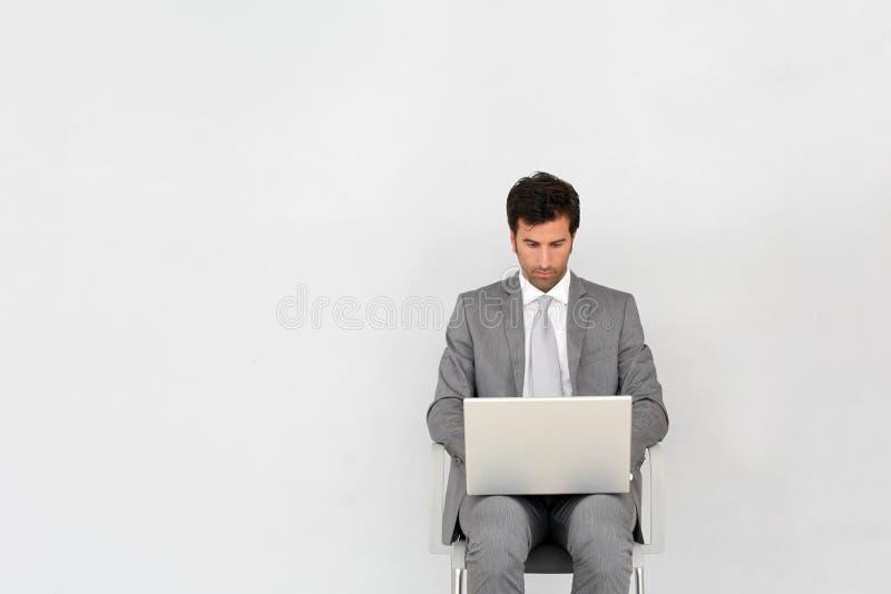 Affärsmansammanträde i väntande rum genom att använda bärbara datorn arkivfoto