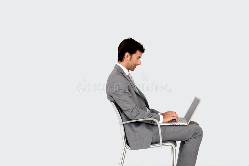 Affärsmansammanträde på stol som arbetar på bärbara datorn royaltyfria foton