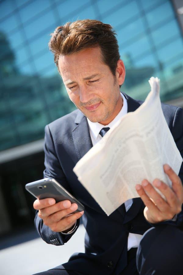 Affärsmansammanträde som läser tidningen och använder utomhus telefonen arkivbild