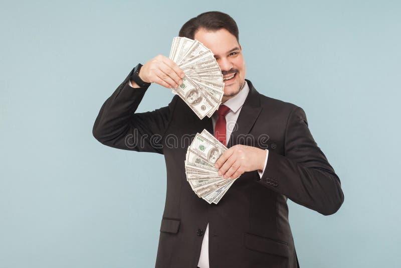 Affärsmanskinn bak fans ut ur pengar arkivfoto