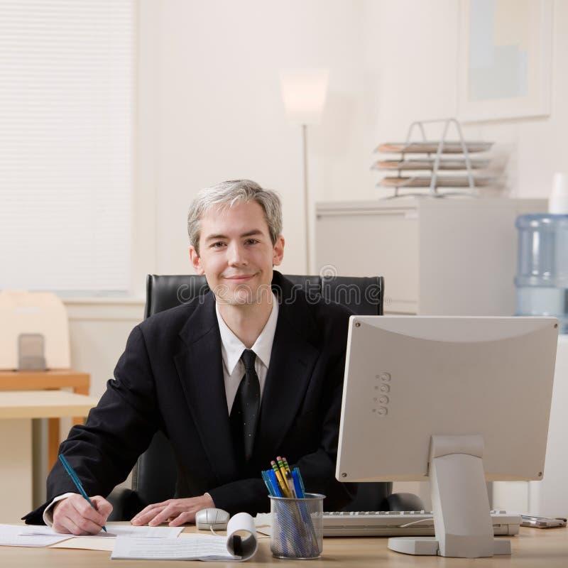 affärsmanskrivbord som ut fyller skrivbordsarbete royaltyfri bild