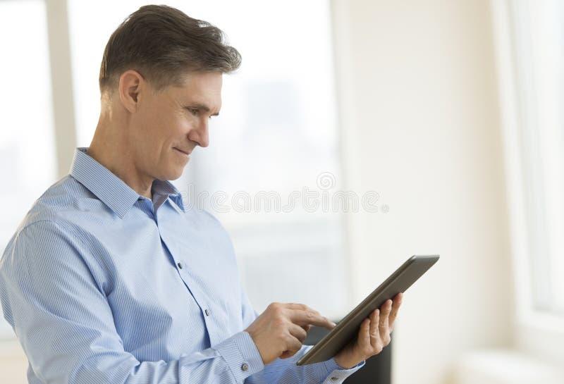 AffärsmanSmiling While Using minnestavla royaltyfri foto
