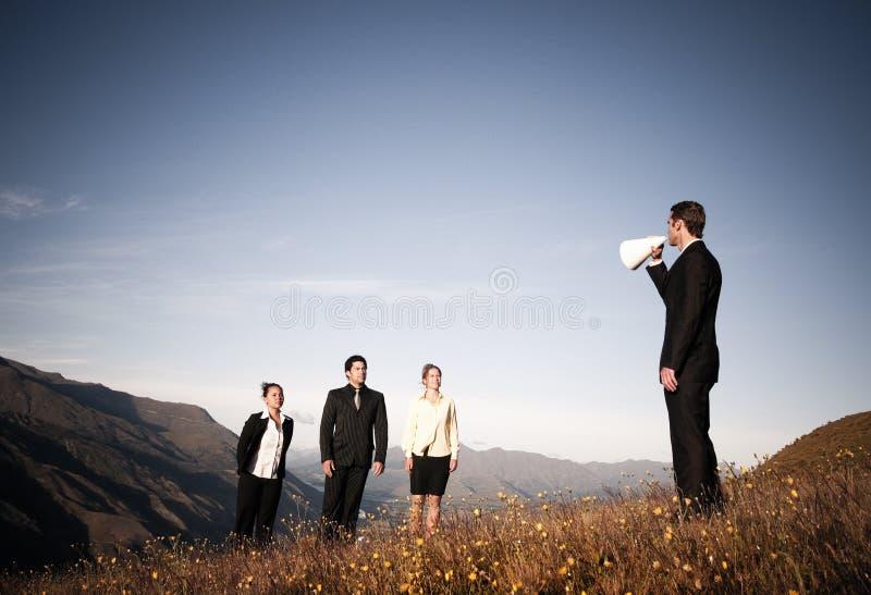 AffärsmanSpeaking Through Paper megafon till affärsfolk royaltyfri foto