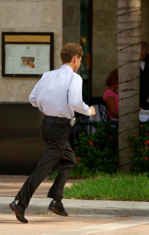 Affärsmanspring över gatan royaltyfria bilder