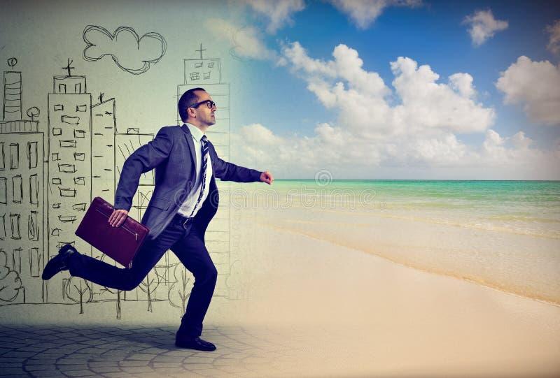 Affärsmanspring i väg från ett liv i en stad till den soliga stranden arkivfoton