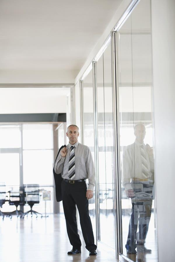 AffärsmanStanding In Office korridor arkivbild