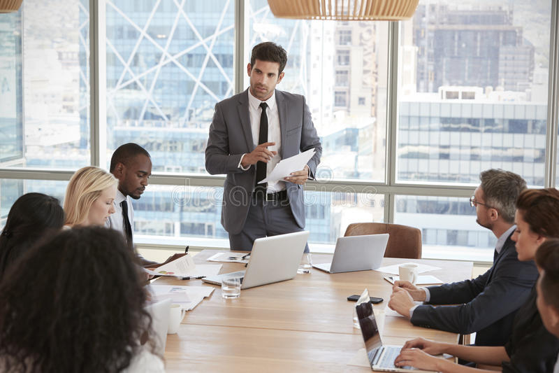 AffärsmanStands To Address möte runt om brädetabellen arkivfoton