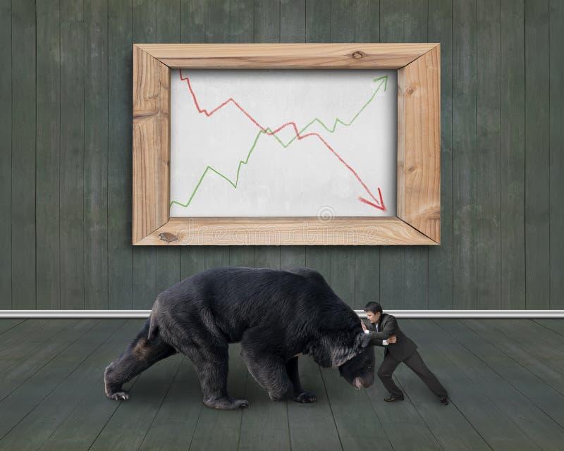 Affärsmanstridighet mot björn med trendlinjer whiteboard royaltyfria foton