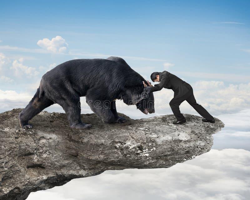 Affärsmanstridighet mot svart björn på klippan med himmel fördunklar royaltyfri fotografi