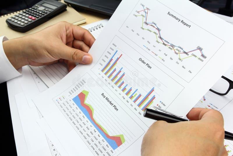 AffärsmanSummary rapport och köpmarknadsplan som analyserar beställning p royaltyfria foton