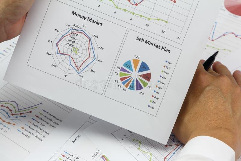 AffärsmanSummary rapport och plan för pengarmarknad som analyserar försäljning royaltyfri bild