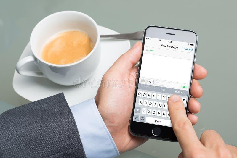 AffärsmanText Messaging On Apple iPhone 6 royaltyfria bilder
