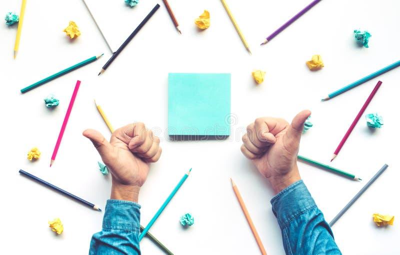 Affärsmantummen upp handen för firar idé med blyertspennan och brevpapper royaltyfria foton