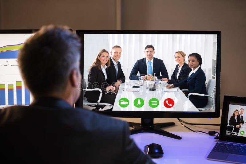 AffärsmanVideo Conferencing With kollegor på datoren arkivfoton