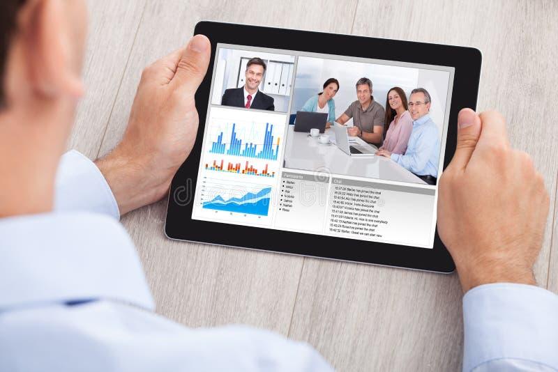 Affärsmanvideoconferencing med laget på den digitala minnestavlan royaltyfria bilder