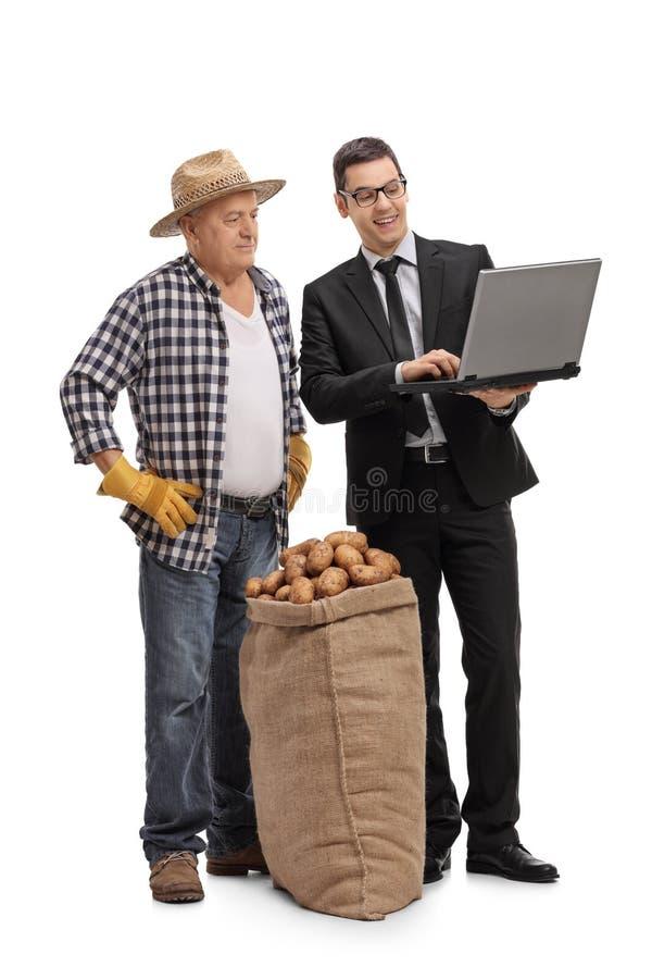 Affärsmanvisning något på en bärbar dator till en bonde royaltyfri fotografi