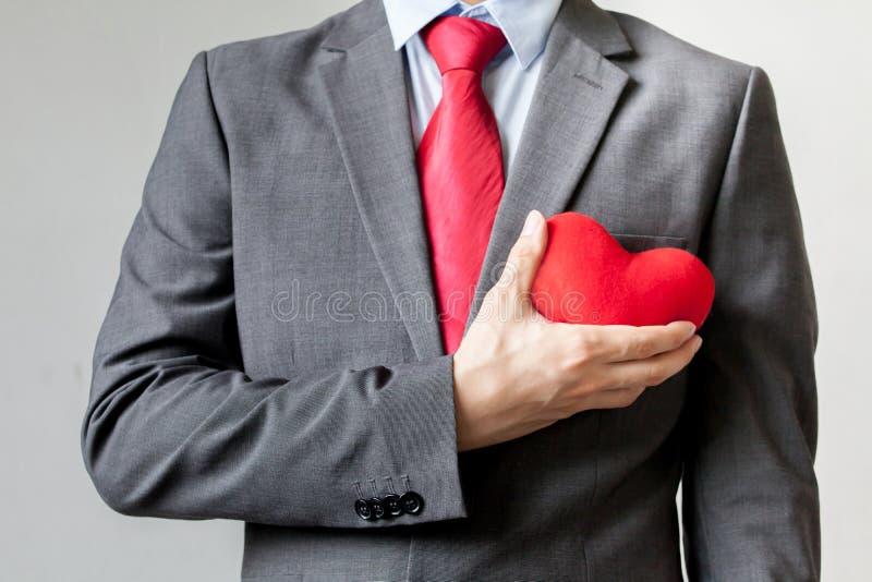 Affärsmanvisningmedkänsla som rymmer röd hjärta på hans bröstkorg i hans dräkt - crm, tjänste- meningsaffärsidé arkivfoto