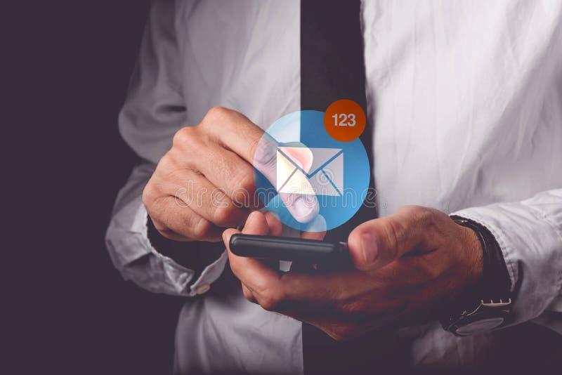 Affärsmanvisningmejl på den mobila smartphonen arkivfoto