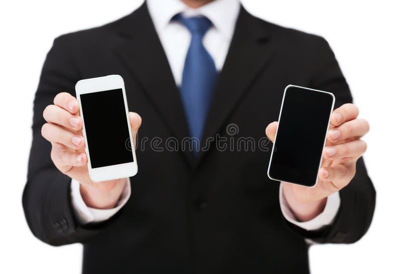 Affärsmanvisningsmartphones med tomma skärmar royaltyfri bild