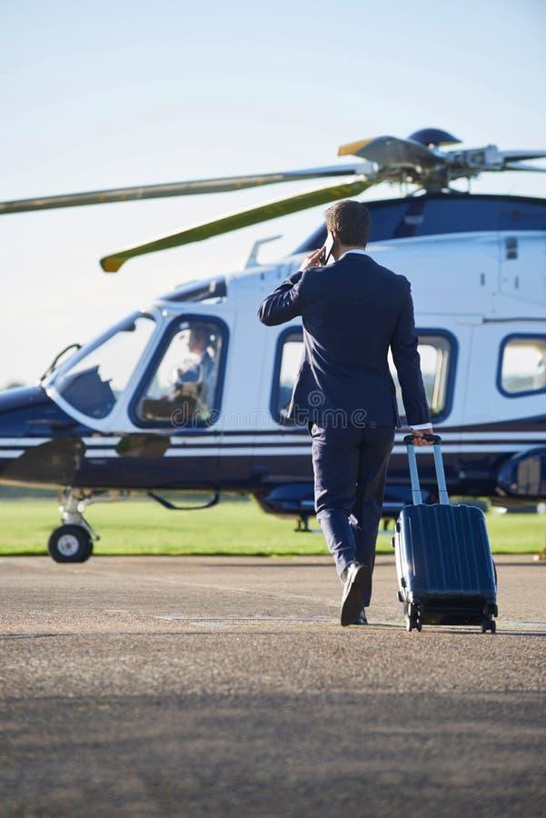 AffärsmanWalking Towards Helicopter stund som talar på mobil arkivbild