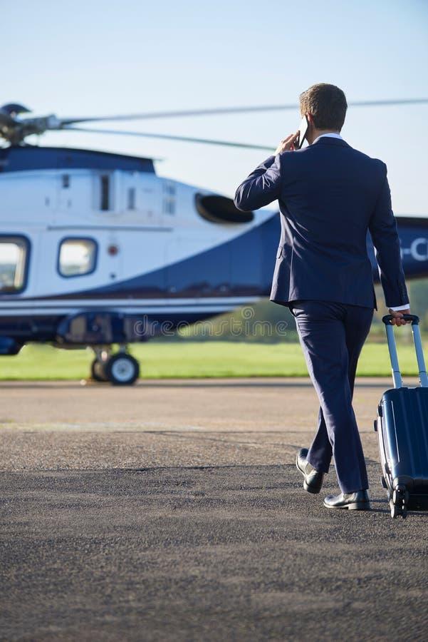 AffärsmanWalking Towards Helicopter stund som talar på mobil royaltyfria bilder