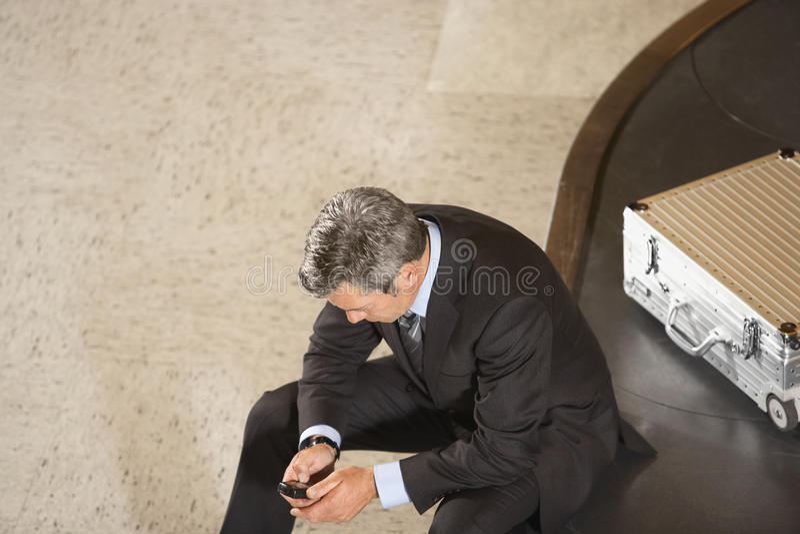 AffärsmanWith Cellphone By bagage på karusell i flygplats arkivfoton