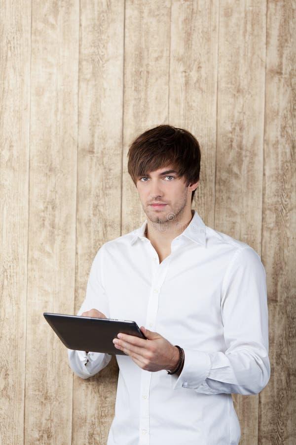 AffärsmanWith Digital Tablet anseende mot trä fotografering för bildbyråer