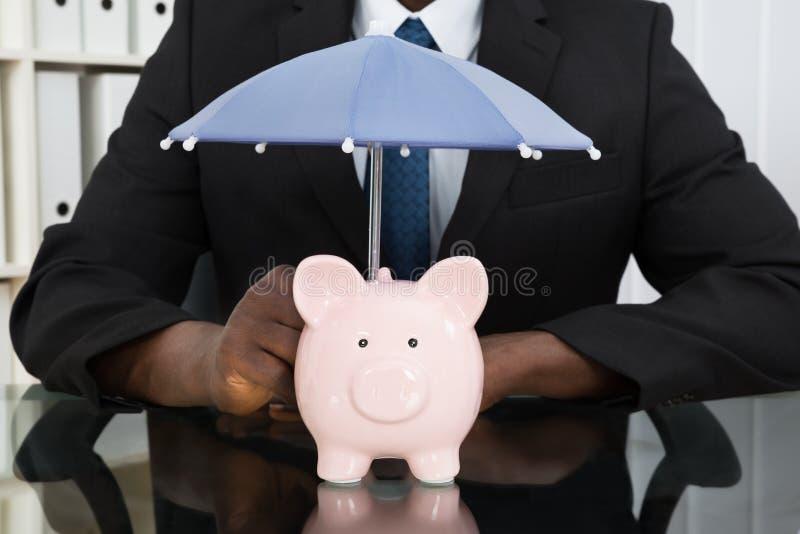 AffärsmanWith Piggybank And paraply arkivbilder