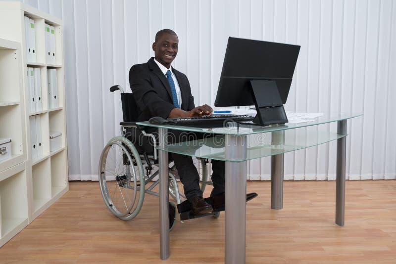 AffärsmanWorking In Office sammanträde på rullstolen arkivfoto