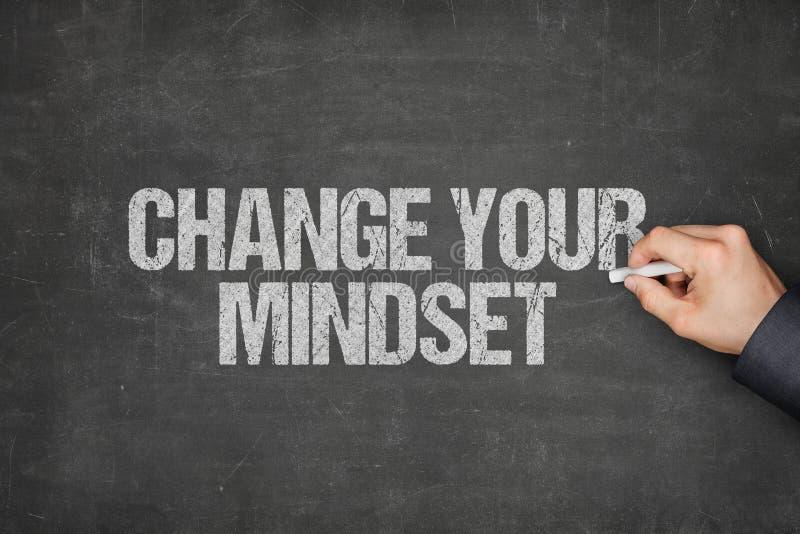 AffärsmanWriting Change Your Mindset på svart tavla arkivbild